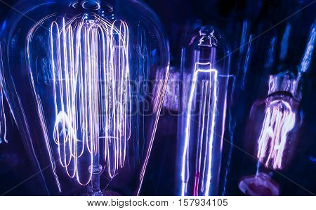 Very Close up Blue Light Bulbs Electricity Surging through Filaments of different sizes and shapes showing the evolution of Technology of Lighting