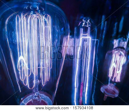 Close up Blue Light Bulbs Electricity Surging through Filaments of different sizes and shapes showing the evolution of Technology of Lighting