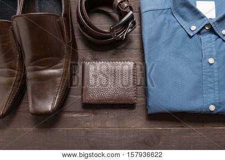 Elegant Set: Brown Men's Shoes, Brown Leather Belt, Blue Shirt, Brown Wallet, On The Wooden Backgrou
