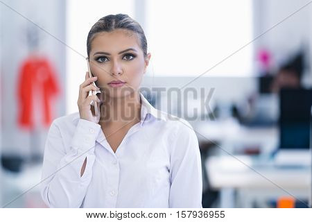 Young woman with mobile phone in the office.