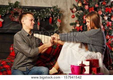 Loving couple and Christmas. Boyfriend wears woolen knit socks on the feet of his girlfriend. In the background a beautiful Christmas tree. Home comfort