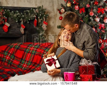 Loving couple and Christmas. Girl hugging boyfriend. She is holding a Christmas gift. In the background a beautiful Christmas tree.