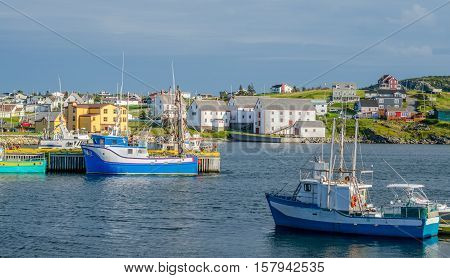 Bona Vista, Newfoundland fishing village.   Boats tied up - in for the day, bright sunshine on calm coastal water. poster