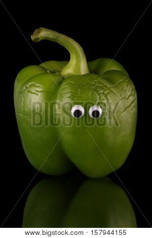 wrinkly green bell pepper with humorous eyes, isolated on a reflective black background. Peppers are a rich source of antioxidants and vitamin c.