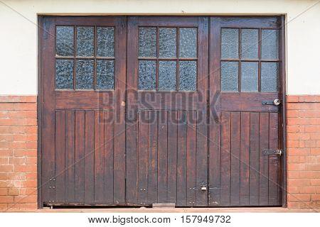 Old wood glass crafted vintage garage doors outside roadside.
