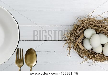 Duck eggs in a grass nest with white plate spoon and fork on white wooden background.