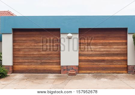 Garage two roll up wood doors for vehicles on roadside entrance.