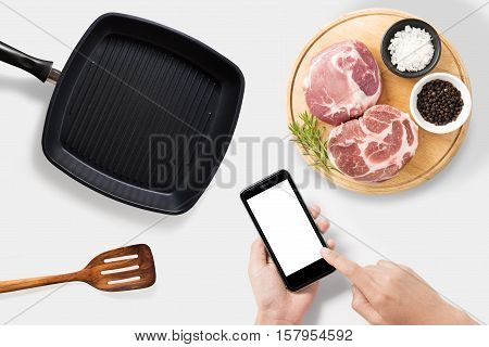 Concept of mockup using smartphone and raw pork chop steak grill pan and spatula set isolated on white background. Clipping Path included on white background.
