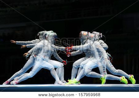 RIO DE JANEIRO, BRAZIL - AUGUST 13, 2016: Ibtihaj Muhammad of United States (R) and Sofya Velikaya of Russia compete in the Women's Sabre Team of the Rio 2016 Olympic Games at Carioca Arena 3