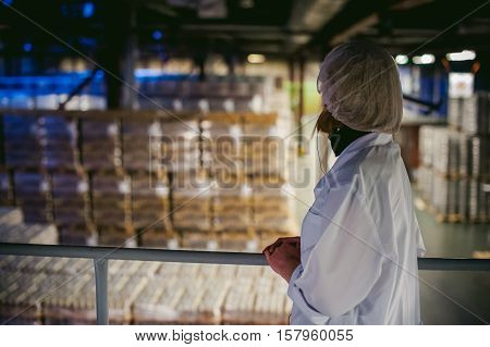 A Woman Employee Of The Warehouse. Woman In A White Robe, Standing In The Warehouse, On The Backgrou