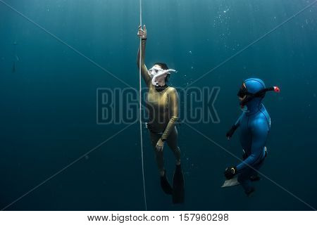 Freedivers ascending along the rope from the depth. Coach watching student