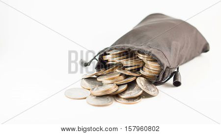 Financial saving and background concept - close up thai baht coins in black bag overflow with copyspace