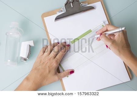 Top view of hands of a female doctor is writing a recipe near a spray inhaler and a space chamber - Medical respiratory disease