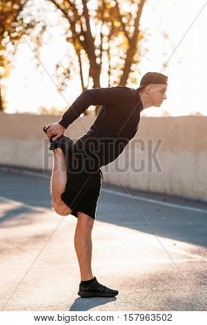 Sprinter warming-up his legs before training on sunset urban background. Young man in sport suit stretching on stadium. Preparation for run.