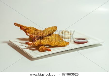 Shot of fried prawns with ketchup and tar tar sauce on white background.