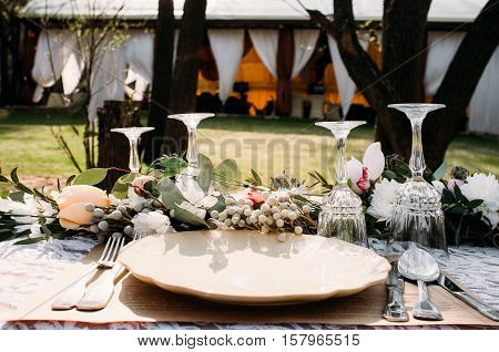 Banquet serving in restaurant, outside. Table prepared for luxury dinner, with porcelain and crystal. Open-air celebration event