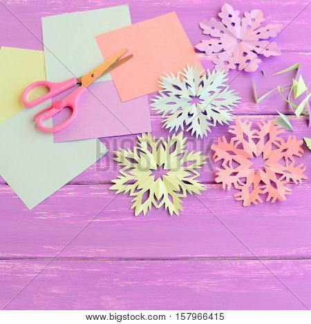Colorful paper snowflakes ornaments, colored paper sheets and scrap, scissors on lilac wooden background. Making snowflakes out of colored paper. Easy winter crafts project for kids