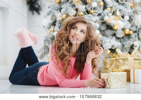 Christmas portrait of beautiful young woman with blue eyes and long curly red hair, light makeup, a beautiful smile, straight white teeth, wearing a pink t-shirt and dark blue jeans posing lying in the background of Christmas tree with gift box