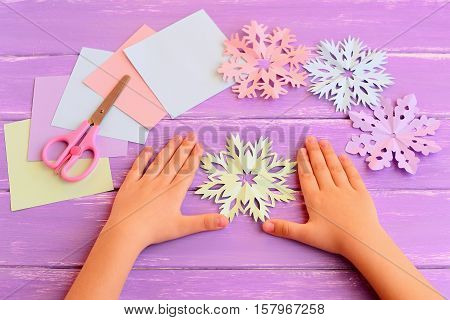 Little kid shows paper snowflakes. Children hands on lilac wooden table. Beautiful colored snowflakes diy cut from paper, paper square sheets, scissors. Easy children winter paper craft idea