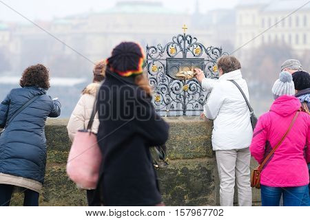 Prague, Czechia - November, 21, 2016: torists near the bas-relief on The Charles Bridge in Prague, Czechia. They believe that if they touch to a bas-relief, they will be accompanied by good luck