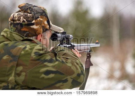 Hunter in camouflage clothes with hunting rifle.