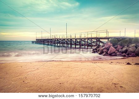 Sunset over the sea bridge in Ravda Bulgaria. Slow motion effect. Old rusty pier against the sunset rays.
