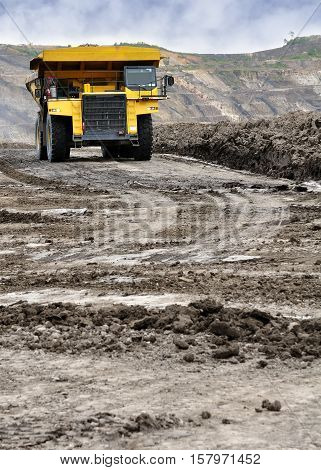 Heavy Truck Coal Mine hauling material through in the mining road