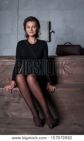 Girl sit and portrait on wood stairs in house.