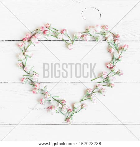 Apple flowers. Heart symbol made of flowers. Top view flat lay square