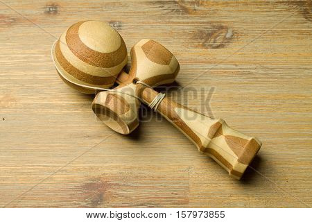 Brown kendama on a wooden table. Traditional japanese wooden toy for agile children. Toy that develops agility and accuracy.