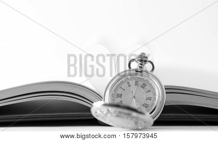 Pocket watch and open book on white