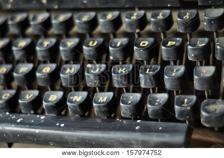 Close up view of antique typewriter keys. The keyboard of the typewriter is visible partially and no human body part is included in the image.