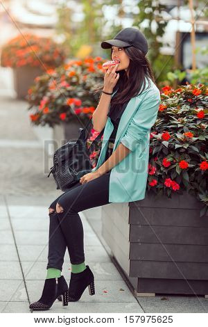 Asian beautiful woman eating a donut sitting near bed of flowers on street, fast food concept outdoors. Busy businessman have no time.