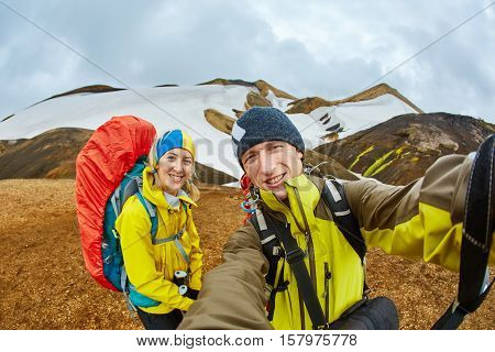 couple joyfull hikers on the trail in the Islandic mountains. Trek in National Park Landmannalaugar, Iceland