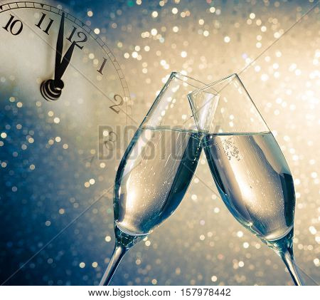 Champagne Flutes With Golden Bubbles On Blue And Golden Light Bokeh Background
