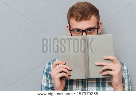 Student in glasses with book in studio. looking at camera. isolated gray background
