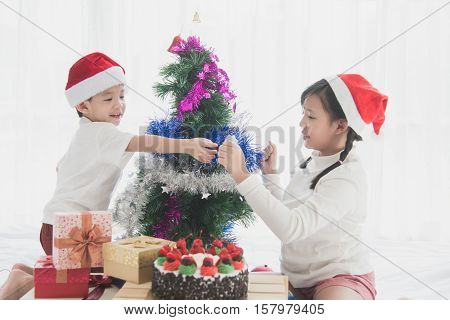 Asian children hanging decorative toy together on christmas tree