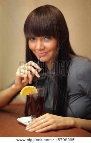 Beautiful young woman drinking mulled wine. poster