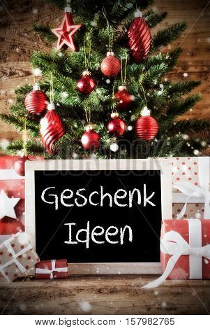 Chalkboard With German Text Geschenk Ideen Means Gift Ideas. Christmas Tree With Balls And Snowflakes. Gifts Or Presents In The Front Of Wooden Background With Bokeh Effect