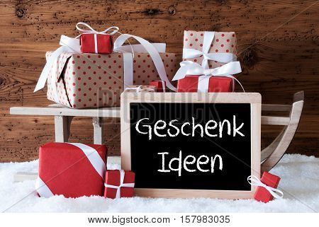 Chalkboard With German Text Geschenk Ideen Means Gift Ideas. Sled With Christmas And Winter Decoration. Gifts And Presents On Snow With Wooden Background.
