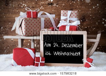 Chalkboard With German Text Am 24. Dezember Ist Weihnachten Means December 24th Is Christmas Eve. Sled With Christmas And Winter Decoration And Snowflakes. Presents On Snow With Wooden Background.