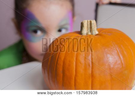 Little cute girl behind pumpkin after making facepaint for halloween party