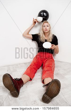 Young beautiful blonde girl with black baloon in hat sitting on floor drinking coffee over white wall. Copy space
