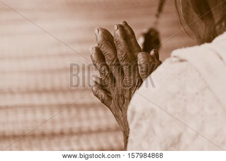 Hand of Old woman praying retro vintage tone