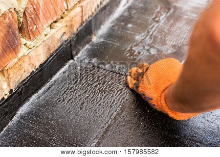 Roofer presses just weld layers of roofing material. Flat roof installation. Heating and melting bitumen roofing felt.