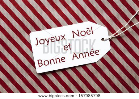 One Label On A Red And Brown Striped Wrapping Paper. Textured Background. Tag With Ribbon. French Text Joyeux Noel Et Bonne Annee Means Merry Christmas And Happy New Year