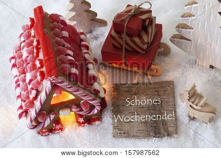Label With German Text Frohe Weihnachten Means Merry Christmas. Gingerbread House On Snow With Christmas Decoration Like Trees And Moose. Sleigh With Christmas Gifts Or Presents.
