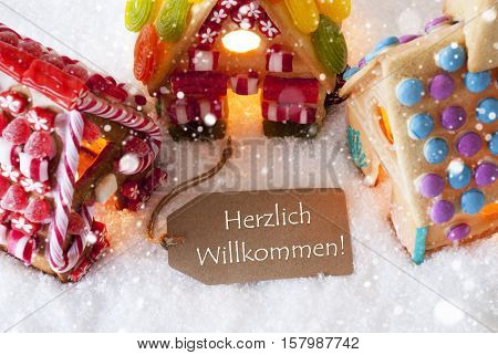 Label With German Text Herzlich Willkommen Means Welcome. Colorful Gingerbread House On Snow And Snowflakes. Christmas Card For Seasons Greetings