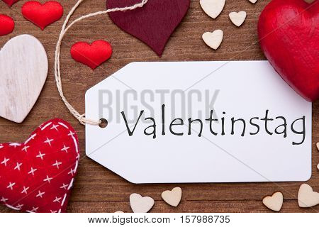 Label With German Text Valentinstag Means Valentines Day. Red Textile Hearts On Wooden Background. Flat Lay With Retro Or Vintage Style