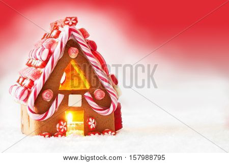 Gingerbread House In Snowy Scenery As Christmas Decoration. Candlelight For Romantic Atmosphere. Red Background With Snow. Copy Space For Advertisement Or Free Text